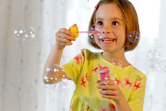Little girl blows soap bubble Stock Image