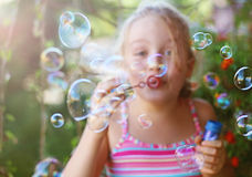 Little girl blows soap bubbles outdoor. Cheerful little girl blows soap bubbles outdoor in summer Royalty Free Stock Images
