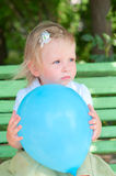 Little girl with blue air balloon Stock Photos