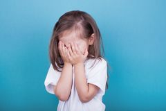 Little girl crying covering her face with her hands stock image