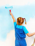 Little girl in blue bib and brace paints the wall Stock Images