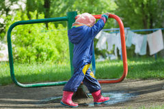 Little girl in blue boilersuit rotating vintage manually roundabout carousel at drying linens and green grass background stock photography
