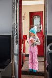 Little girl in blue cap and winter pants tarvelling by old train Kukushka in Georgia between Bakuriani and Borjomi royalty free stock image