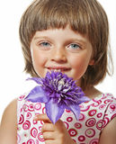 Little girl with blue clematis flower Royalty Free Stock Photography