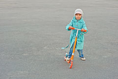 Little girl in blue cloak riding Royalty Free Stock Images
