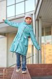 Little girl in blue coat walking on Stock Image
