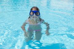 Little girl with blue diving glasses in an outdoor pool. Little girl with blue diving glasses coming out of the water in an outdoor pool in summer stock image
