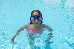 Little girl with blue diving glasses in an outdoor pool. Smiling little girl with blue diving glasses in an outdoor pool in summer royalty free stock photo