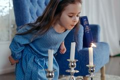 The little girl in a blue dress blows out the candles. blue armchair in the background royalty free stock image