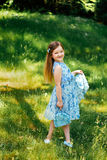 Little girl in a blue dress with a blue bag in summer garden Stock Photography