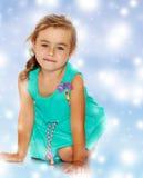 Little girl in blue dress on her knees Stock Image