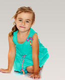 Little girl in blue dress on her knees Stock Photo