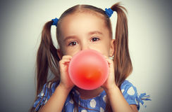 Little girl in blue dress inflates red balloon Stock Photos
