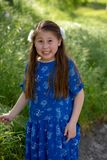 Little Girl in Blue Dress making funny and crazy face in front of green field stock photo