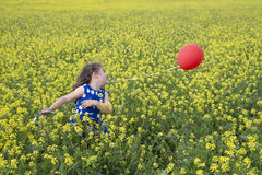 Little girl in blue dress playing with red flying balloon in yel Stock Photo