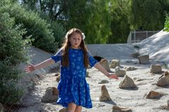 Little Girl in Blue Dress playing in storm drain at park by stones royalty free stock photo