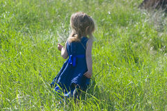 Little girl in a blue dress running away Royalty Free Stock Photography