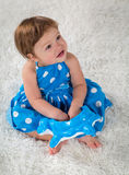 Little girl in a blue dress sits on the bed and looks up Royalty Free Stock Image