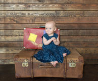 The little girl in blue dress sits on big suitcase. Stock Photo