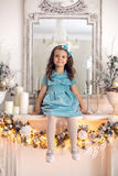 Little girl in a blue dress sits stock photo