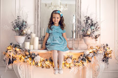 Little girl in a blue dress sits royalty free stock photo