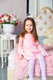 Little girl in blue dress sitting on the couch Royalty Free Stock Image