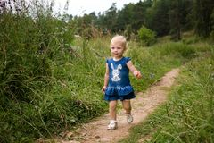 A little girl walks alone along the path. Summer day, wildflowers royalty free stock photos
