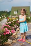 Little girl in blue dress watering flowers with a Royalty Free Stock Images
