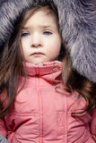 Little girl with blue eyes. Little girl in the jacket with fur hood Stock Photos
