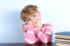Little girl with blue eyes with apple and books Royalty Free Stock Photography