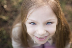 Little Girl With Blue Eyes. Close-up girl's face, photographed from above. With a smile on her face and beautiful blue eyes looking at the camera Stock Image