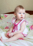 Little girl with blue eyes in a pink dress sitting on the bed Royalty Free Stock Image