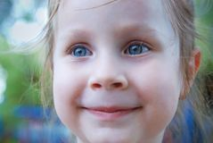 Little Girl with Blue Eyes Smiling over Blured Summer Background. stock photography
