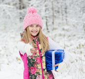 Little girl with blue gift box showing thumbs up in winter forest Stock Photos