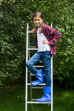 Little girl in blue gumboots standing on stepladder at apple gar Royalty Free Stock Image