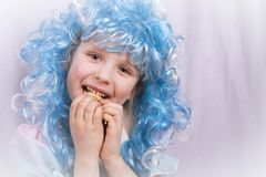 Little girl with blue hair eating cookie Royalty Free Stock Photography