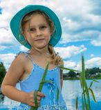 Little girl in a blue hat. With a green spike in hand on the background of the river Stock Image