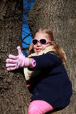 Little girl with blue jacket and pink sunglasses hugging the tree Royalty Free Stock Photos