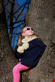 Little girl with blue jacket and sunglasses sitting on the tree and looking up Stock Photos