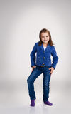 Little girl in blue jeans and jacket posing in the studio Stock Photo