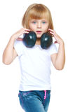 Little girl in blue jeans. Little girl listening to music on headphones.Isolated on white background Royalty Free Stock Photos