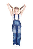 Little girl in blue overalls. Holding her ponytails up Royalty Free Stock Images