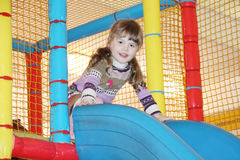 Little girl on blue plastic slide Royalty Free Stock Photography