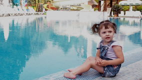 Little girl by the blue pool. A small child is playing by the pool. A beautiful little girl is sitting on the edge of a stock footage