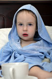 Little girl in a blue robe resting on the bed Royalty Free Stock Images