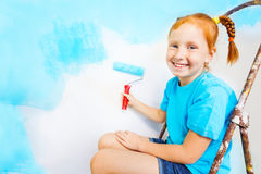 Little girl in blue shirt sits on a ladder Royalty Free Stock Image