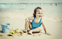Little girl in blue swimsuit is playing in water Stock Photo