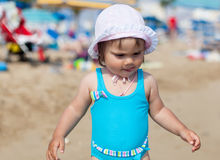 Little girl in blue swimsuit is playing in water Royalty Free Stock Image