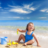 Little girl in blue swimsuit is playing in water Royalty Free Stock Photos