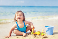 Little girl in blue swimsuit is playing in water Stock Photos